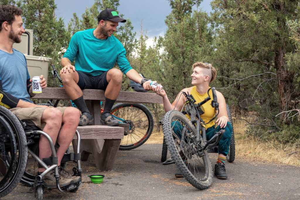 man in wheelchair and girl on handcycle having a beer